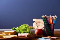 回到学校概念,学校用品,饼干,包装了午餐和饭盒在白色书桌,选择聚焦,特写镜头上 免版税库存图片