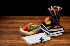 回到学校概念,学校用品,饼干,包装了午餐和饭盒在白色书桌,选择聚焦,特写镜头上 库存图片