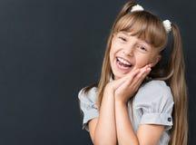 回到学校概念-看照相机的欢呼的女孩 库存图片