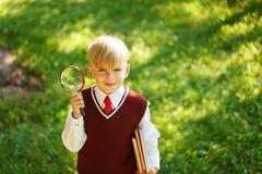 回到学校的逗人喜爱的男孩 有书和寸镜的孩子在第一个教学日 库存图片