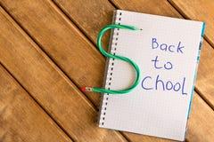 回到学校的题字在木背景的笔记薄的 免版税库存图片