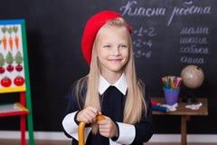 回到学校!女小学生站立在有统治者的黑板 女小学生回答教训 在白垩b附近的一个一年级学生 免版税库存照片