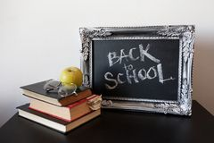 回到学校,在葡萄酒框架的白垩 在黑板的文本和堆课本 免版税库存图片