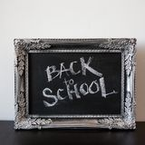 回到学校,在葡萄酒框架的白垩 在黑板的文本 免版税库存照片