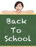 回到学校,有黑板的年轻学生女孩 免版税库存照片