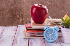 回到学校,笔记本,闹钟,红色苹果,在木的花 免版税库存照片