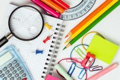 回到学校:在一张白色书桌上的学校用品 免版税库存图片