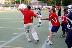 回到教练橄榄球赛拿着s小组美国妇女 图库摄影