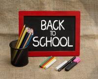 回到有铅笔和文具项目的学校黑板 免版税库存照片