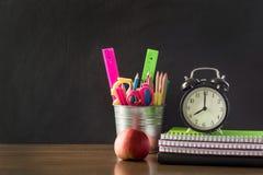 回到概念学校 学校用品、闹钟和苹果 复制在黑板的空间 免版税库存照片