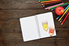 回到概念学校 打开笔记本和苹果与色的铅笔,姜饼在木背景 免版税库存照片
