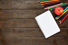 回到概念学校 打开笔记本和苹果与色的铅笔,姜饼在木背景 库存图片