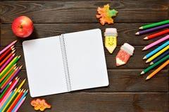 回到概念学校 打开笔记本和苹果与色的铅笔,姜饼在木背景 免版税库存图片