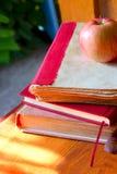 回到概念学校 有书的在木背景的黑板和苹果 免版税图库摄影
