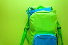回到概念学校 有学校用品的绿色背包在绿色背景 顶视图 复制空间 图库摄影