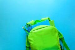 回到概念学校 有学校用品的绿色背包在蓝色背景 顶视图 复制空间 库存照片