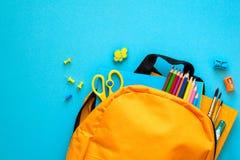回到概念学校 有学校用品的背包 顶视图 复制空间 定调子 免版税库存照片
