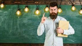 回到概念学校 有胡子的行家拿着书,在背景的黑板 衬衣的指向有胡子的人  图库摄影