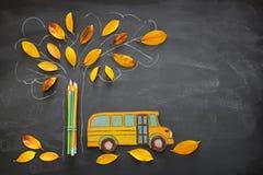 回到概念学校 校车的顶视图在树剪影旁边的图象和铅笔与秋天烘干在教室blackbo的叶子 免版税库存图片