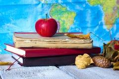 回到概念学校 老葡萄酒书和苹果和秋叶在geografic地图背景 免版税库存图片