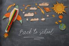 回到概念学校 迅速上升,空间元素形状裁减从纸和绘在教室黑板背景 免版税图库摄影