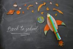 回到概念学校 迅速上升,空间元素形状裁减从纸和绘在教室黑板背景 库存照片