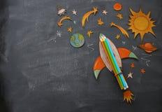 回到概念学校 迅速上升,空间元素形状裁减从纸和绘在教室黑板背景 免版税库存图片