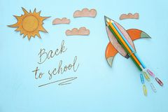 回到概念学校 迅速上升,空间元素形状裁减从纸和绘在木蓝色背景 免版税库存照片