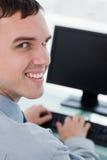 回到观点的使用监控程序的一个微笑的生意人 库存照片