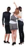 回到视图三个年轻人女商人指向。 免版税库存图片
