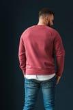 回到视图 一个年轻有胡子的英俊的男性行家,打扮在有长的袖子和牛仔裤的一件红色套头衫,站立户内 库存图片