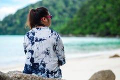 回到视图 亚洲妇女佩带的太阳镜和靛蓝衬衣sittin 免版税图库摄影