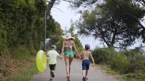 回到视图 在夏天晴天照顾和她的走在公园的两儿子在海滩附近 泳装和a的一个少妇 股票录像