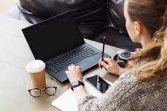 回到视图 年轻女实业家在运作的办公室坐手提电脑 候宰栏 成人的企业教育 免版税库存照片