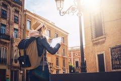回到视图 年轻旅游妇女帽子的和有背包的在城市街道上站立和寻找在地图的一个方式 免版税库存照片