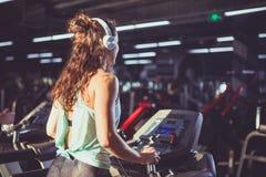 回到视图 有豪华的卷发的美丽的妇女在背心和麋在踏车、心脏训练机器和减重的健身房跑 免版税库存照片