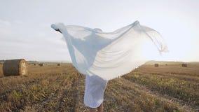 回到视图 礼服的美丽的女孩有运行在领域附近到日落和举手的薄绸的围巾的-在夏天 股票视频
