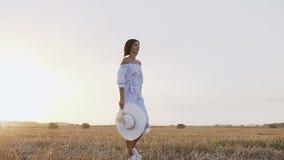 回到视图 走在领域的一串足迹在日落的一名年轻深色的妇女 一件长的蓝色礼服的可爱的女孩有帽子的 影视素材