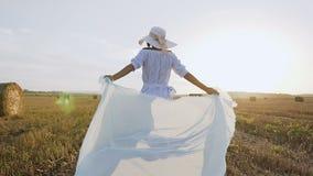 回到视图 长的礼服的美丽的女孩有运行在与大包秸杆的夏天领域的薄绸的围巾的到日落和 股票视频