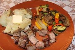 回家做的牛排,用被烘烤的土豆和烤 免版税库存照片