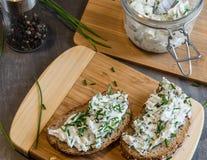回家做的面包在一个木切板用凝乳酪和乳清干酪和草本 装饰用绿色草本 免版税图库摄影