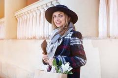回家从春天礼物从男朋友开花的大学holdinf的侈奢的女孩 外套的少妇 免版税图库摄影