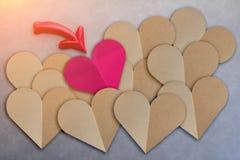 回收与红色箭头的纸心脏在灰色皮革背景 库存图片