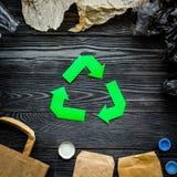 回收在废料纸,塑料,在灰色木背景顶视图的聚乙烯中的绿皮书标志 免版税库存图片