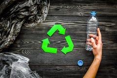 回收塑料和聚乙烯废物 Botlles和袋子在绿色附近回收标志在灰色木背景顶视图 图库摄影