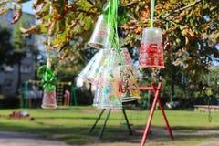 回收塑料瓶和杯子项目,上色用不同的颜色 塑料的第二生活 孩子项目在后院 免版税库存图片