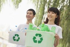 回收塑料瓶的两青年人 免版税库存照片