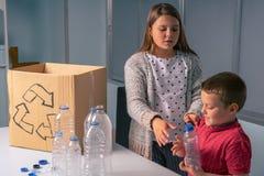 回收瓶和塑料盖帽,滑稽的态度的孩子 免版税库存图片