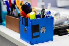 回收用于商店供应的软盘,创造性的对象例如笔铅笔剪刀在桌上的一个箱子在工作办公室 库存图片