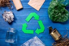 回收的垃圾与回收在蓝色木背景顶视图的标志 库存照片